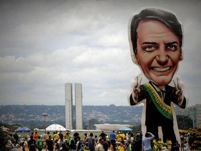 Seguidores del presidente electo, Jair Bolsonaro, caminan frente a un muñeco gigante con su figura en la Explanada de los Ministerios.
