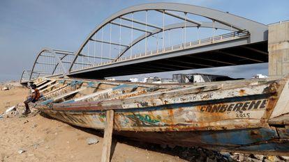 Un chico permanece sentado en un cayuco de pescadores junto a un puente a medio construir en Dakar, Senegal, el 13 de julio de 2020.