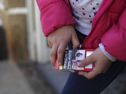 Natasha, de ocho años, sujeta un paquete de tabaco .