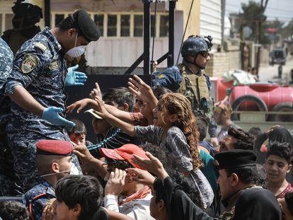 La policía iraquí reparte bolsas con alimentos básicos y suministros durante la cuarentena en el suburbio de Ciudad Sáder, Bagdad, este lunes.