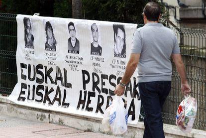 Un hombre pasa frente a un cartel de presos de ETA en el barrio bilbaíno de Uribarri en una imagen de 2019.