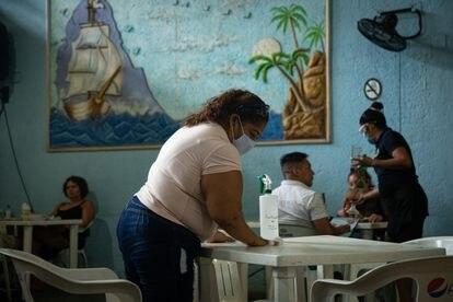 Una mujer hace la limpieza de las mesas en un restaurante el pasado octubre.