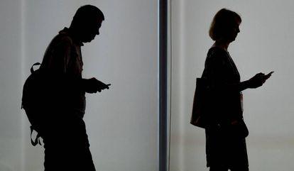 Dos personas usando sus teléfonos móviles.