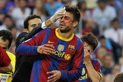 Piqué, con la cara ensangrentada, es atendido por el doctor tras sufrir un golpe en la cabeza.