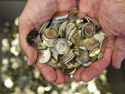 Un hombre sostiene varias monedas de euro en una imagen de archivo.