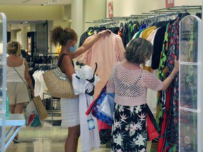Clientas en una tienda de ropa en agosto.