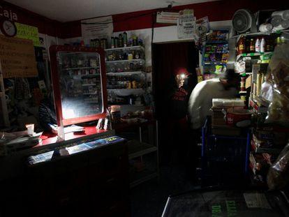 Un cliente es auxiliado por el empleado de una tienda con la luz de su celular en la ciudad de Monterrey, Nuevo León.