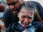 A protester reacts after being hit by pepper spray from police as their group of demonstrators are detained prior to arrest at a gas station on South Washington Street, Sunday, May 31, 2020, in Minneapolis. Protests continued sparked by the death of George Floyd, who died after being restrained by Minneapolis police officers on May 25.  (AP Photo/John Minchillo)