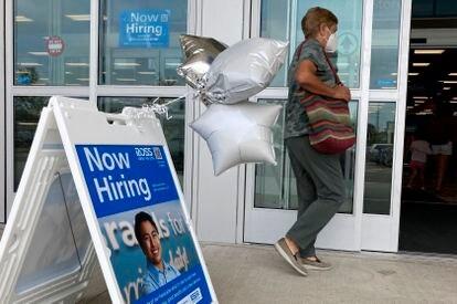 Una mujer junto a un letrero de contratación antes de ingresar a una tienda minorista en Morton Grove, Illinois.