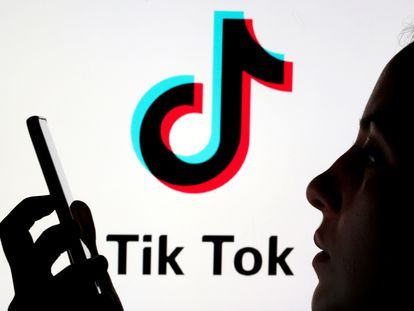 Un joven sostiene su móvil ante un logo de TikTok.