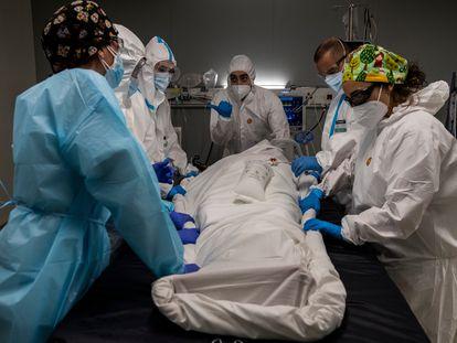 Dvd 1039 (04/02/21). Reportaje sobre el Hospital de pandemiasdestinado a pacientes COVID-19  Isabel Zendal de Madrid.En la imagen, varios sanitarios manipulan a un paciente en una UCI.  FOTO: Carlos Rosillo.