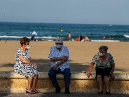 Tres personas mayores descansan en el paseo marítimo de la playa de la Malvarrosa (Valencia).