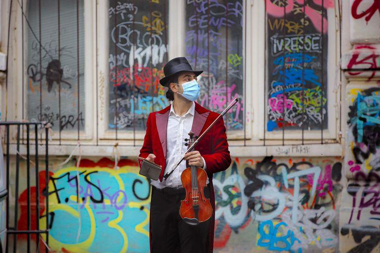 Un músico preparado para tocar con mascarilla en una calle de Bucarest (Rumanía).