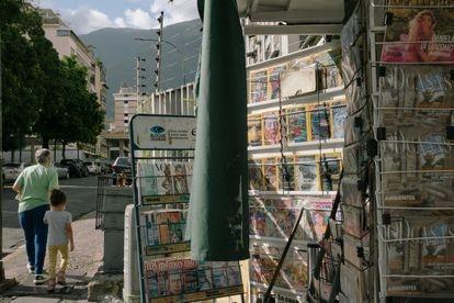 Peatones pasan frente a un kiosco en Caracas que antes vendía periódicos y ahora solo vende revistas.