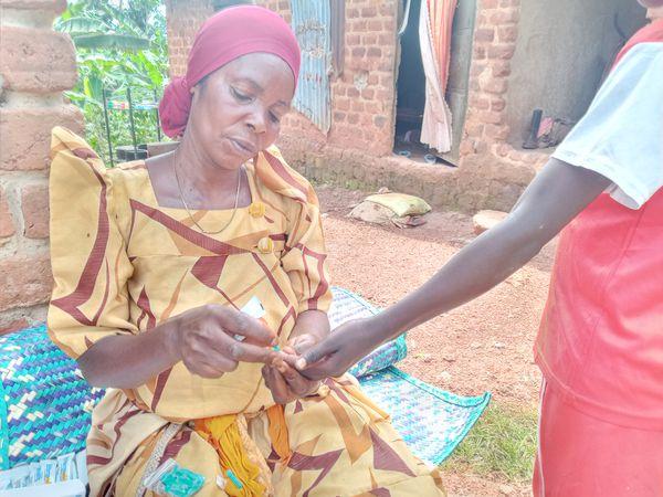 Aisha Nanfuka realiza un test a una niña de su comunidad.