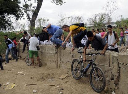 Un grupo de personas salta un muro que separa Colombia de Venezuela.