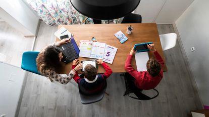 Una madre ayuda a sus hijos con los deberes mientras teletrabaja en un municipio de la Comunidad de Madrid.