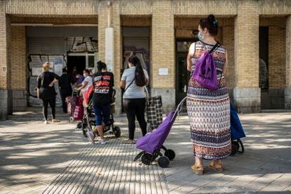 Un grupo de mujeres espera su turno en un local del Banco de Alimentos en el barrio de Orcasitas, Madrid.