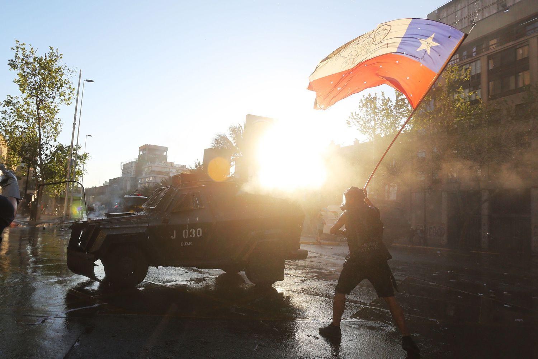 Un manifestante ondea una bandera chilena, este viernes en una protesta en vísperas del plebiscito constitucional.
