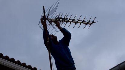 Una operario ajusta la antena en un tejado de Colmenar Viejo (Madrid).