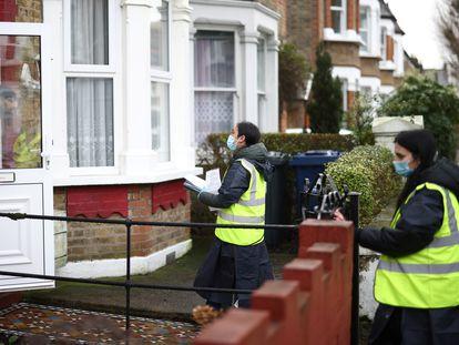 Dos voluntarias entregan puerta a puerta test caseros para hacerse la prueba del coronavirus, en Londres, este miércoles.