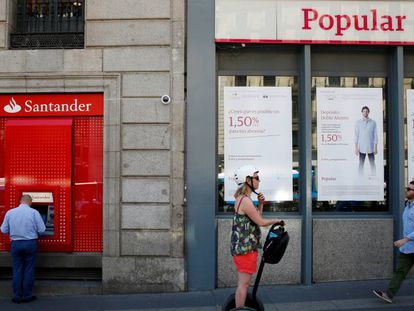Una oficina del Banco Popular junto a un cajero del Santander, en Madrid.