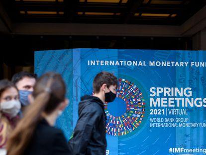 Varios jóvenes pasan ante la sede del FMI en Washington, este lunes.