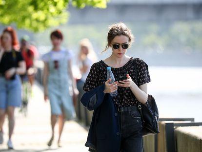 Una mujer mira el móvil mientras camina.