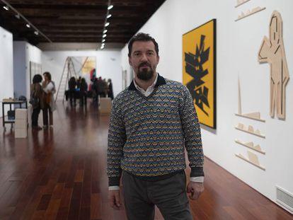 Miki Leal, este jueves en Sevilla en la muestra 'El abrazo'. A la derecha, las obras de Palazuelo (lienzo) y de Pereñiguez.
