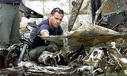 Un policía revisa los restos de uno de los dos coches bomba que explotaron ayer en el centro de Jerusalén, una de las zonas más vigiladas de Israel.