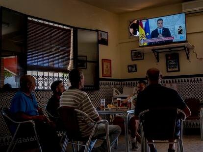 Varios clientes de un bar de Sevilla ven por televisión la comparecencia del presidente del Gobierno, Pedro Sánchez, tras el Consejo de Ministros