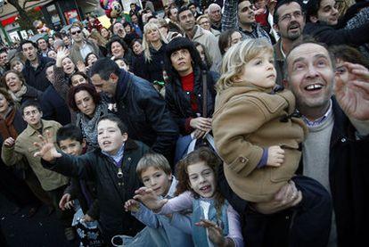 Niños con sus familiares miran a los Reyes Magos durante la cabalgata del 5 de enero de 2011 en Sevilla.