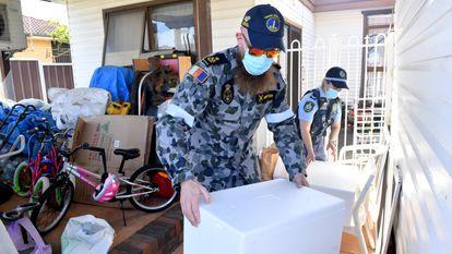 Personal de la Fuerza de Defensa Australiana entregan paquetes de alimentos a las personas que se encuentran en confinamiento, en el suburbio de Fairfield, en el suroeste de Sídney, este lunes.