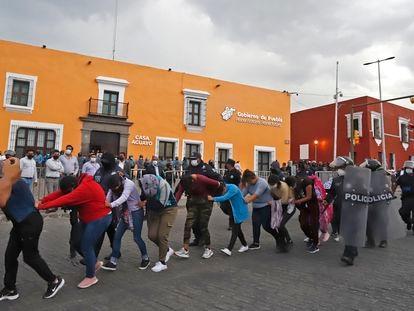 Elementos de la policía estatal desalojan a estudiantes de la Escuela Normal Rural Carmen Serdán, en Puebla.