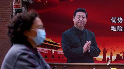 Una mujer pasa frente a un cartel con la imagen de Xi Jinping en Shanghái.