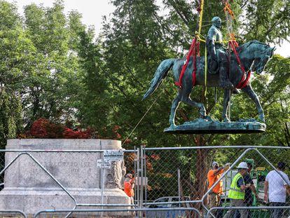 Trabajadores retiran la estatua de Lee, que será puesta bajo resguardo hasta que los concejales decidan su futuro.