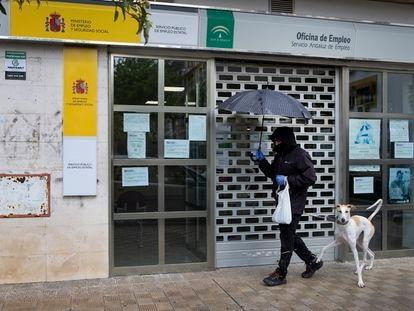Un hombre pasa con su perro por delante de una oficina de empleo cerrada, este mes de abril en Sevilla.