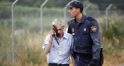 Un policía acompaña al maquinista Francisco José Garzón, poco después del accidente del tren Alvia.