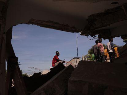 Un grupo de personas remueve escombros en una calle de Los Cayos.