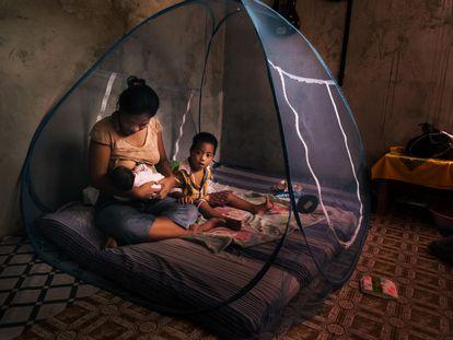 Una mujer amamanta a su bebé dentro de una mosquitera para protegerse del mosquito que transmite la malaria.