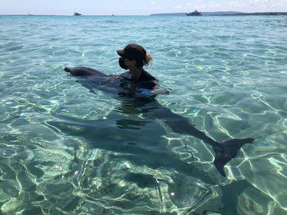 La agente balear de Medio Ambiente Pepita Cardona sujeta al delfín moribundo en la playa de Llevant de Formentera el pasado 20 de julio.