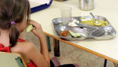 Una niña almuerza en un comedor escolar.