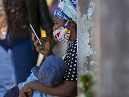 Una mujer consulta su móvil sentada en un banco en Johanesburgo, en Sudáfrica.