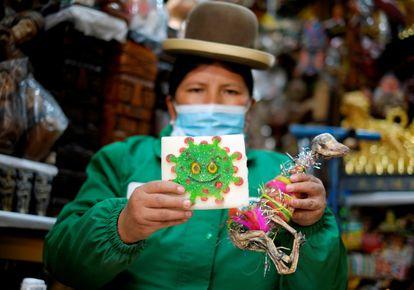 Victoria Acarapi sostiene una figura del coronavirus y un feto de llama como parte de una ofrenda en el mes de la Pachamama en un mercado de La Paz, Bolvia en 2020.