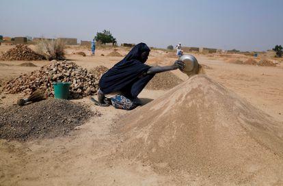 Ouedraogo Rasmata, quien huyó de los ataques de militantes armados en la región del Sahel de Soum, prepara la arena para venderla a los trabajadores de la construcción en un campamento informal para personas desplazadas en las afueras de Ouagadougou, Burkina Faso, el 19 de noviembre de 2020.