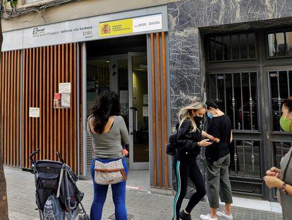 Varias personas hacen cola a las puertas de una oficina del Servicio Valenciano de Empleo y Formación (Servef).