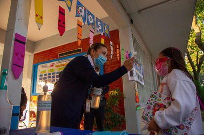 Un maestro toma la temperatura de un estudiante antes de ingresar al aula.