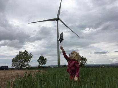 Una niña juega junto al aerogenerador instalado por los socios de Viure de l'aire del cel en Pujalt (Barcelona).