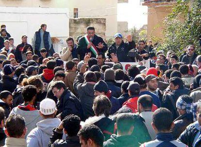 El alcalde de Lampedusa, Bernardino de Rubeis, se dirige a un grupo de<i> sin papeles</i> amotinados en la isla italiana el pasado 24 de enero.