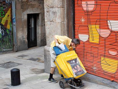 Un cartero deja correo en un local cerradode Barcelona, el 30 d ejunio de 2020.